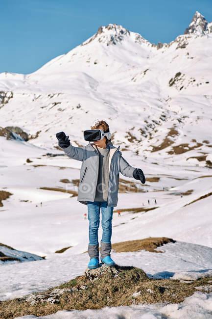 Corpo pieno di allegro ragazzo divertente in outwear in piedi sulla neve ed esplorare la realtà virtuale nella soleggiata giornata invernale in montagna — Foto stock