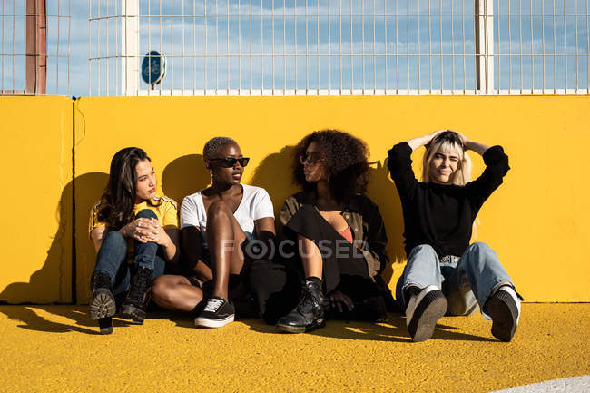 Cheerful young multiracial female students enjoying pastime on stadium — Stock Photo