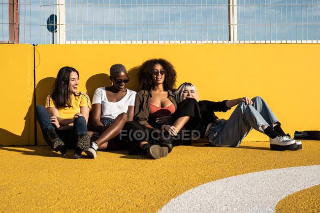 Fröhliche junge multirassische Studentinnen genießen Zeitvertreib im Stadion — Stockfoto