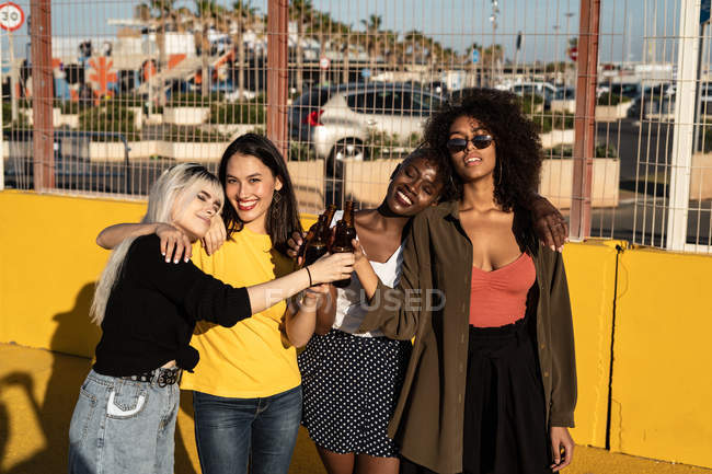 Happy relaxed multiracial charming women in casual clothes clinking glasses and hugging while drinking beer and standing in sunlight on stadium — Stock Photo