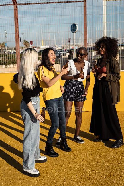 Cheerful young diverse female friends celebrating meeting in city — Stock Photo