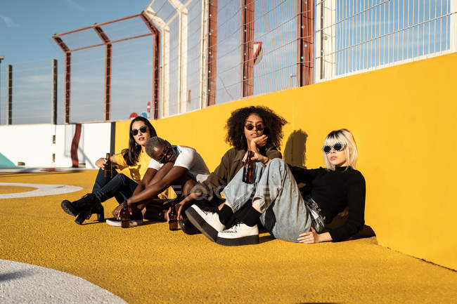 Focused young diverse women in trendy clothes and sunglasses looking at camera while sitting during friendly meeting on stadium — Stock Photo