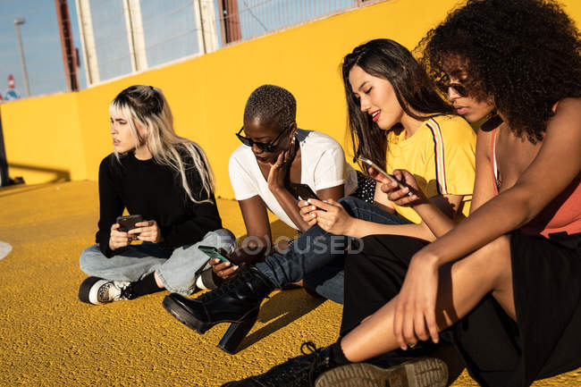 Carefree young multiracial female friends using smartphone in stadium — Stock Photo