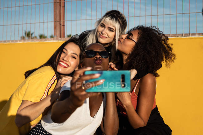 Carefree youthful multiracial women in casual clothes enjoying freedom and taking selfie on cellphone while spending time on stadium — Stock Photo