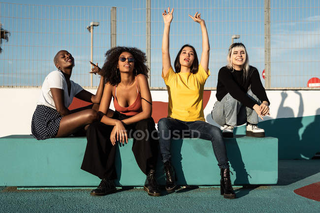 Careless youthful diverse women in casual clothes having fun together on stadium — Stock Photo