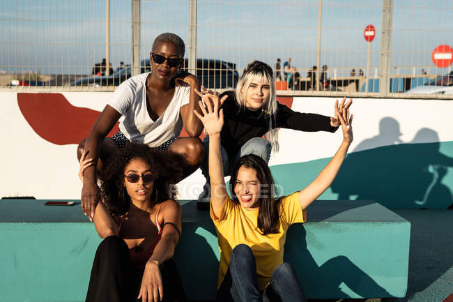 Cheerful young multiracial female friends enjoying free time in street — Stock Photo