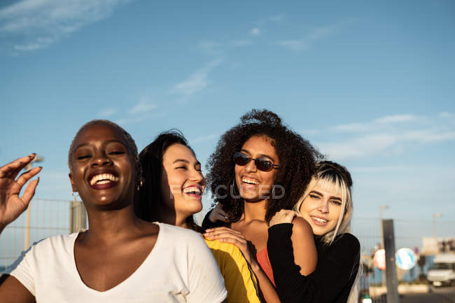 Confident young multiethnic female friends enjoying pastime in street — Stock Photo