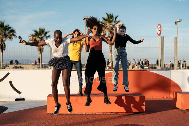 Счастливые молодые подруги-представительницы разных рас в повседневной одежде, наслаждающиеся парой, прыгая со скамьи на стадионе — стоковое фото