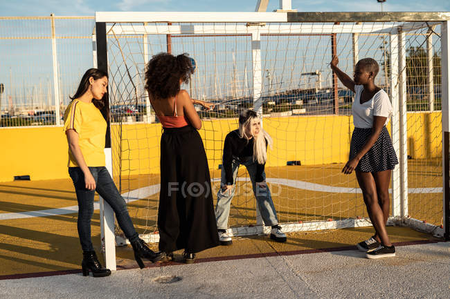 Focused young multiracial female friends spending free time together in stadium — Stock Photo