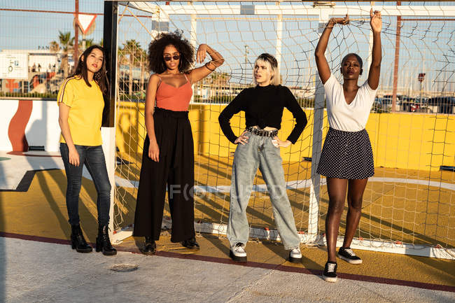 Carefree youthful diverse women in casual clothes standing at football gates in stadium — Stock Photo