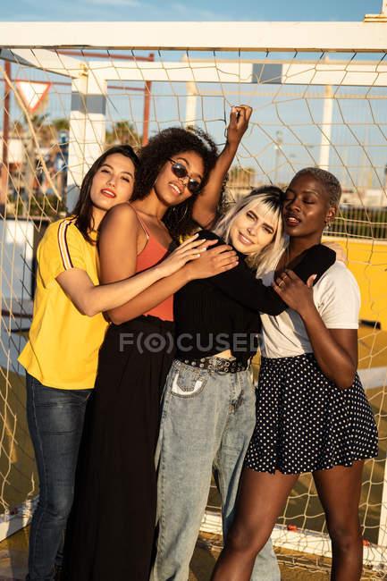 Focalizzato giovani amici femminili multirazziali trascorrere del tempo libero insieme nello stadio — Foto stock