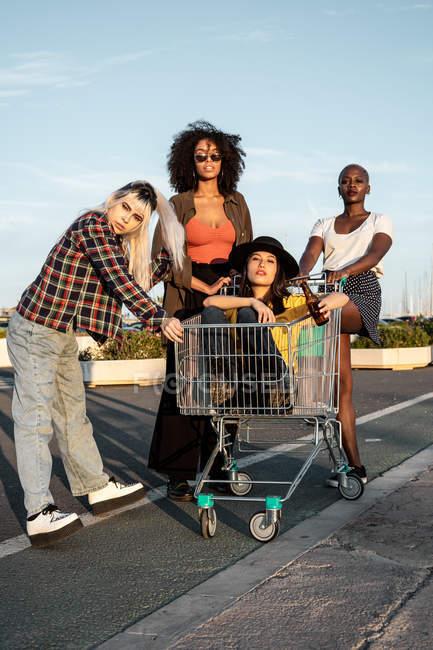 Diverse junge Freundinnen in lässiger Haltung mit leerem Einkaufswagen für Witze stehen herum und schauen in die Kamera — Stockfoto