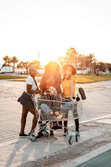 Grupo multirracial de jovens mulheres em pé em torno de carrinho de compras na estrada — Fotografia de Stock
