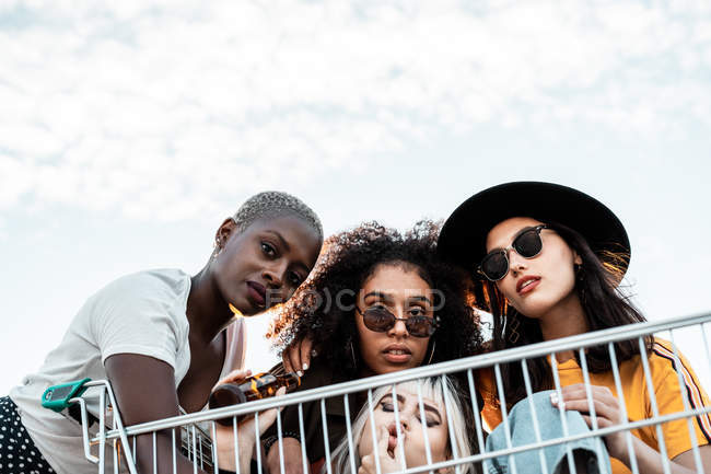 Multiracial group of young women standing around shopping cart on road — Stock Photo