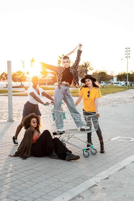 Многорасовая группа молодых женщин, стоящих вокруг тележки с покупками на дороге — стоковое фото