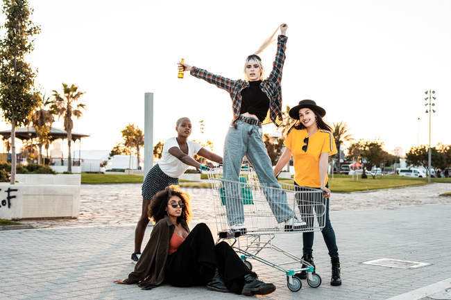 Gruppe junger Frauen steht um Einkaufswagen herum auf der Straße — Stockfoto