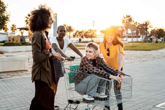 Groupe multiracial de jeunes femmes debout autour du chariot sur la route — Photo de stock