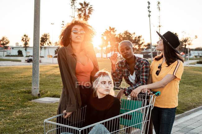 Gruppo multirazziale di giovani donne in piedi intorno carrello della spesa su strada — Foto stock