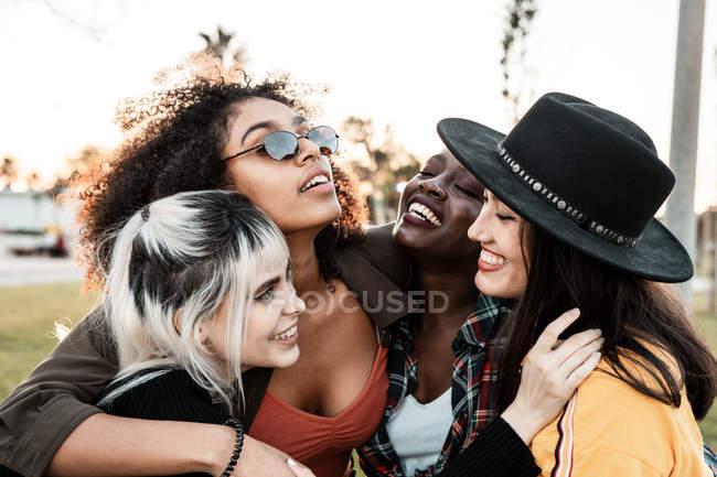 Retrato de grupo de diversas jovens mulheres vestindo roupas em estilo hipster olhando umas para as outras com sorrisos e abraços juntos — Fotografia de Stock