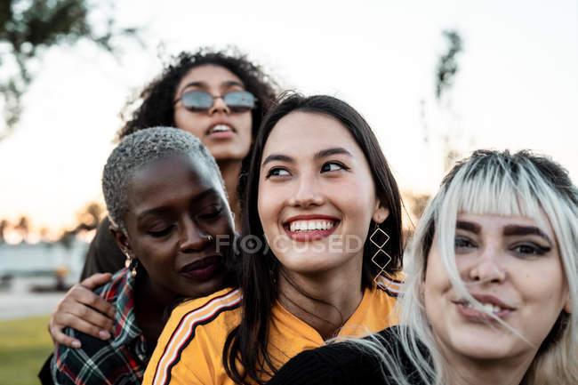 Diverse lächelnde Frauen, die sich auf dem Rasen umarmen — Stockfoto