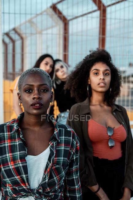 Різна група жінок, які носять одяг у гіпстерському стилі, дивиться на камеру серйозно, стоячи в міському районі поруч з металевим парканом. — стокове фото