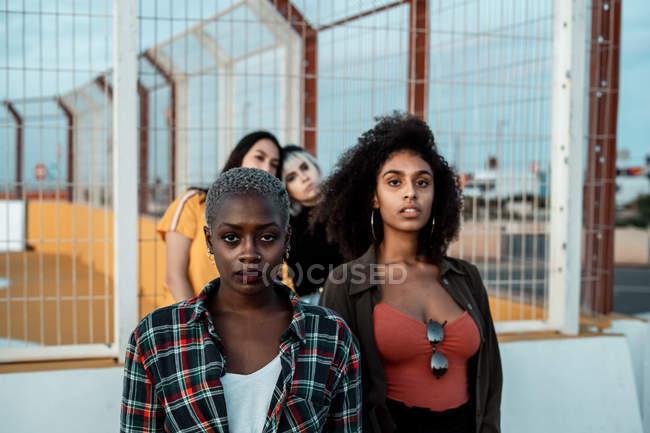 Etnica giovani donne in abiti casual guardando la fotocamera con occhi impavidi — Foto stock