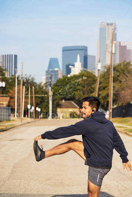 Hispanic male runner in active wear stretching and warming up before practice in downtown Dallas, USA — Stock Photo