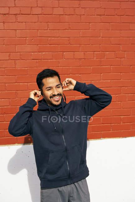 Задоволений латиноамериканець у повсякденному одязі посміхається і озирається, насолоджуючись музикою за допомогою навушників на вулиці міста Далласа, штат Техас. — стокове фото