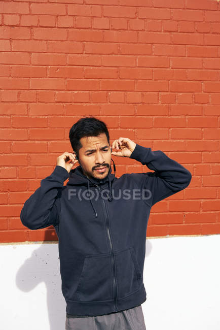 Contenuto Uomo ispanico in abbigliamento casual sorridente e distogliendo lo sguardo mentre si gode la musica con gli auricolari in strada a Dallas, Texas — Foto stock