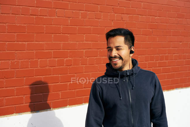 Content Hispanic man in casual wear smiling and looking away while enjoying music using earphones at city street in Dallas, Texas — Stock Photo