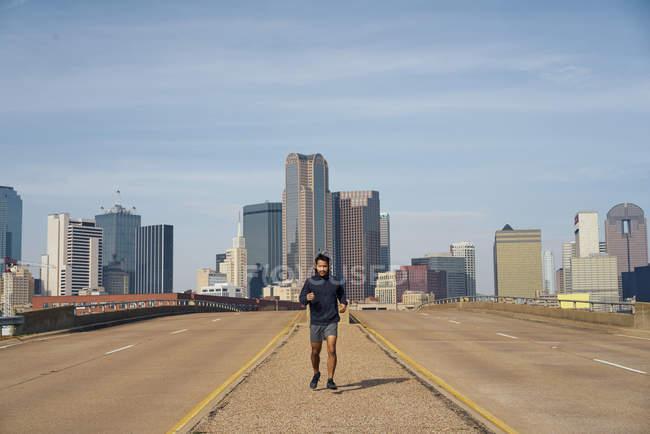 Латиноамериканец-бегун в повседневной толстовке в наушниках во время бега с голубым небом над центром Далласа, штат Техас — стоковое фото