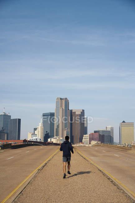Rückansicht eines anonymen männlichen Joggers in lässigem Kapuzenpulli, der bei blauem Himmel über der Innenstadt von Dallas, Texas läuft — Stockfoto