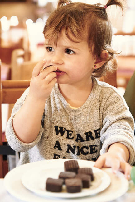 Baby girl sitting and eating — Stock Photo