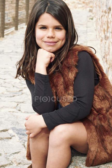 Girl in waistcoat sitting on road border in park — Stock Photo