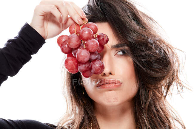 Fashionable young woman holding grapes — Stock Photo