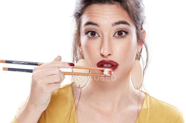 Senhora com maquiagem moderna degustação de alimentos com pauzinhos — Fotografia de Stock