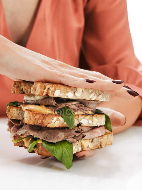 Mujer anónima con sabroso sándwich doble en las manos - foto de stock