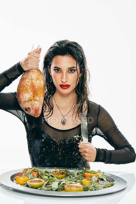 Preciosa mujer con pescado y cuchillo en las manos en la mesa - foto de stock