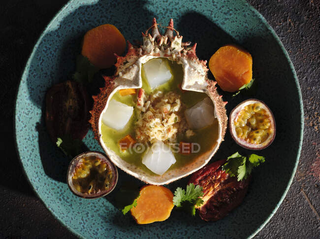 Delectable ceviche served in spider crab shell with arthropod meat and fruits on plate in restaurant — Stock Photo
