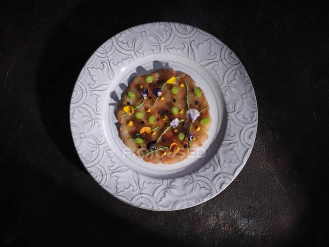 Vista dall'alto di condimenti tritati e petali su tappo piatto di fungo servito su piatto rotondo su superficie nera — Foto stock