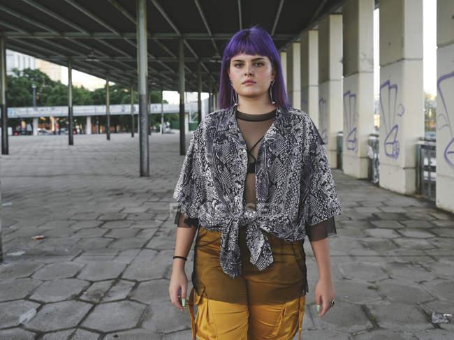 Модная стильная женщина с фиолетовой прической в желтых брюках смотрит в камеру на улице — стоковое фото