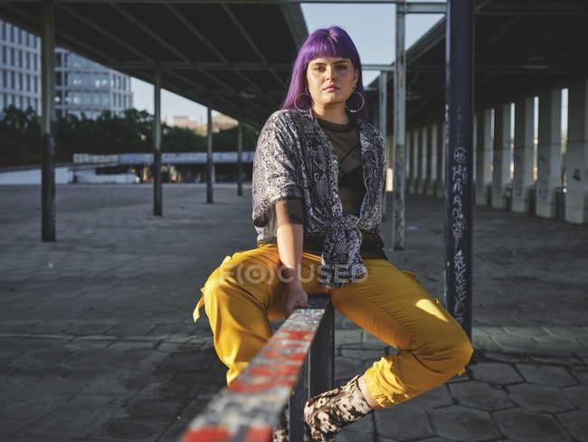 Stilvolle Frau mit leuchtend lila Frisur in gelben Hosen sitzt auf Metallzaun in der City Station und blickt in die Kamera — Stockfoto