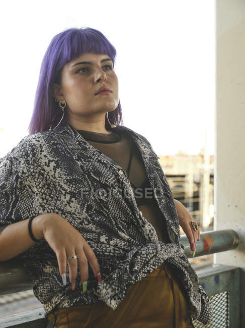 Fashion stylish woman with purple hairstyle looking away and leaning on railing — Stock Photo