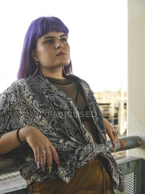 Модная стильная женщина с фиолетовой прической, отводящая взгляд и опирающаяся на перила — стоковое фото