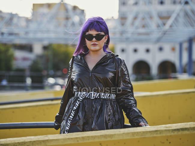 Femme confiante à la mode aux cheveux violets vêtue d'une veste noire brillante et de lunettes de soleil regardant à la caméra le point de vue de la ville — Photo de stock
