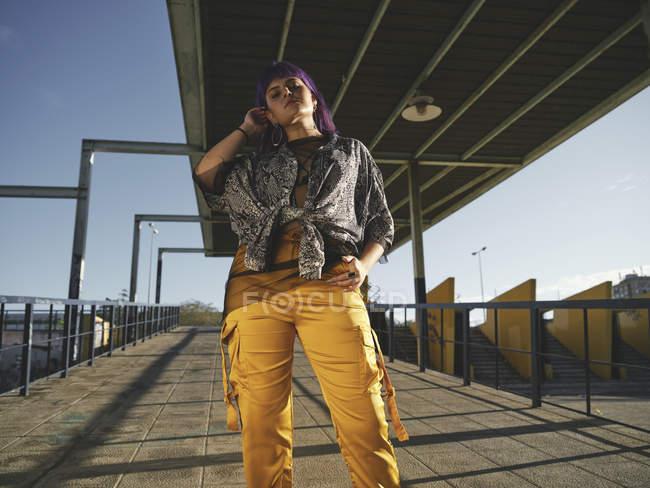 Снизу модная стильная женщина с фиолетовой прической, смотрящая в камеру на улице — стоковое фото