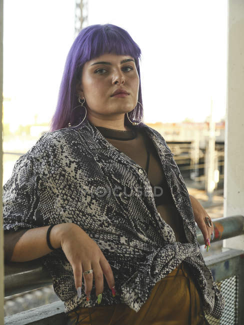 Fashion stylish woman with purple hairstyle looking in camera and leaning on railing — Stock Photo