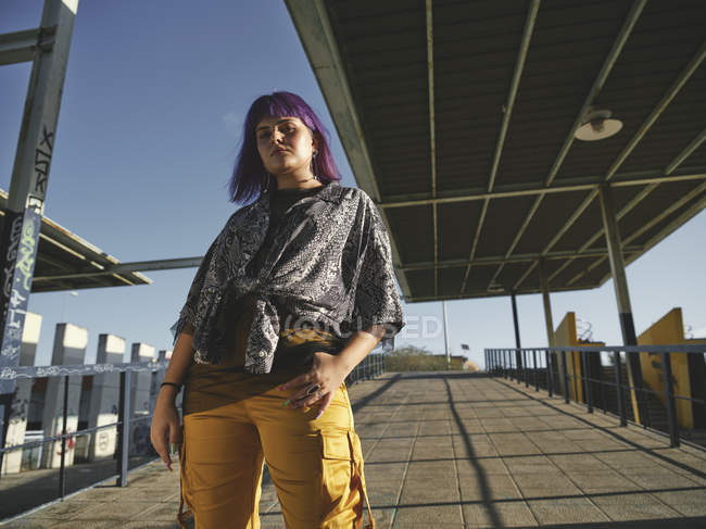 Stylish woman with purple hairstyle in yellow pants standing in street and looking in camera — Stock Photo
