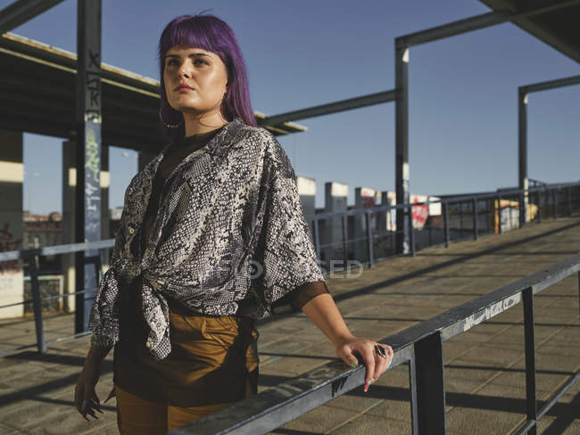 Stylish woman with purple hairstyle in fashionable jacket in street in bright daytime — Stock Photo