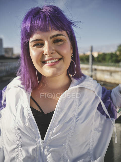 Fashion stylish woman with purple hairstyle in city center confidently looking in camera and smiling — Stock Photo